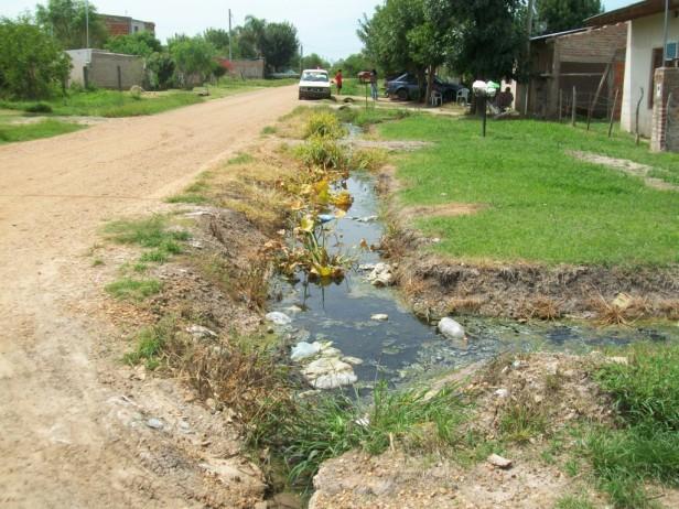 Agua servida en cunetas frente a la Escuela N° 63 del barrio 25 de Mayo